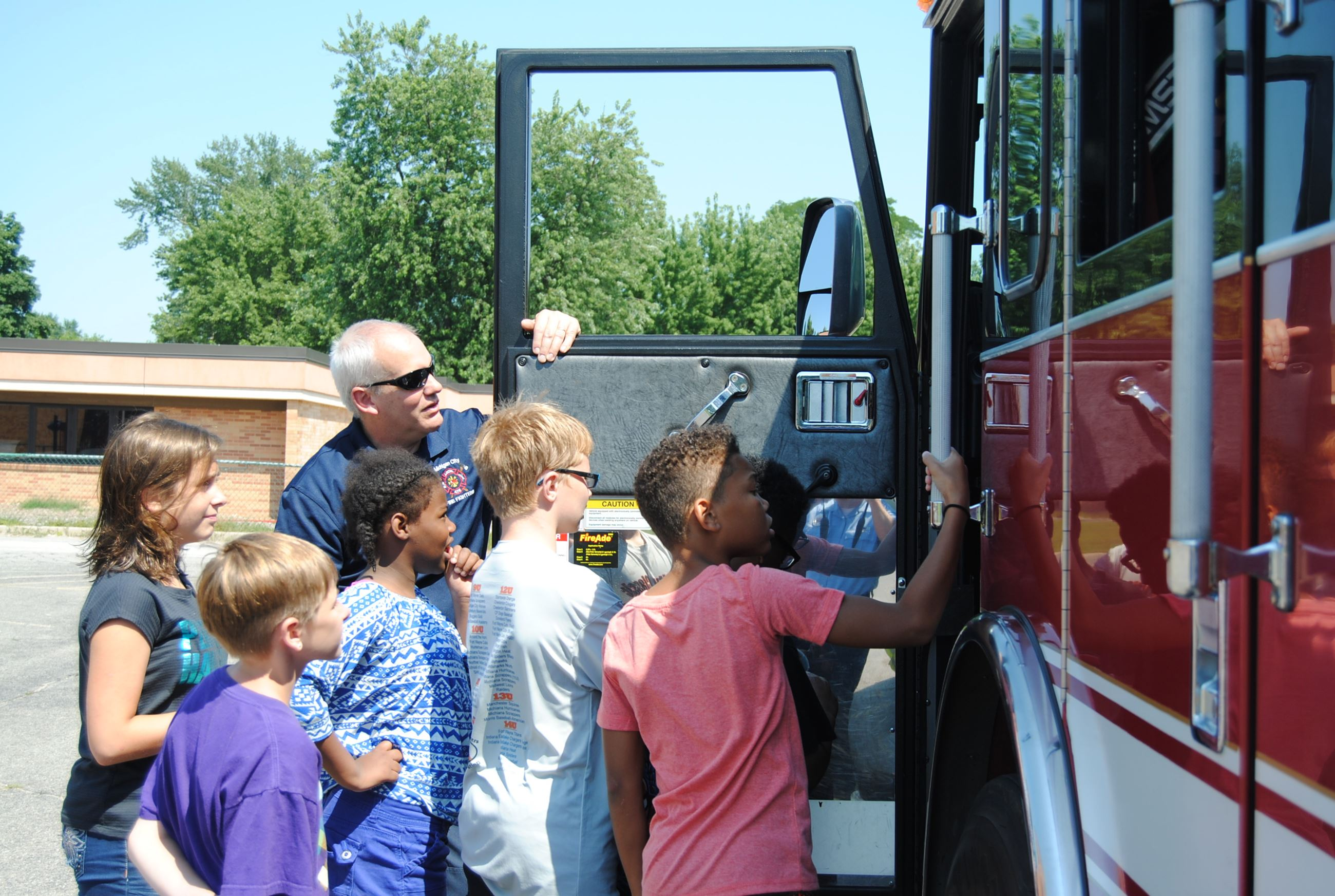 Firefighter shows Engine interior to students from Knapp Elementary